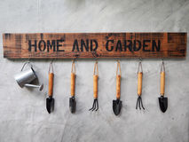 Gardening tools hang on the concrete wall Stock Photos