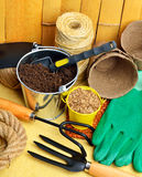 Gardening tools, peat cups, thread; seeds in tins against fence Stock Images