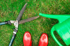 Gardening tools, red garden shoes, secateurs,  watering can on the grass,  close up. Royalty Free Stock Photos