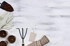 Gardening Tools and Seedling Peat Pots. Gardening tools, seeds and soil on a white wooden table. Image shot from above in flat lay style Stock Image