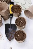 Planting Vegetable Seeds in Seedling Peat Pots. Gardening tools, seedling peat pots, seeds and soil on a white wooden table. Image shot from above in flat lay Royalty Free Stock Photo