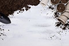 Planting Seeds Background with Seedling Peat Pots. Gardening tools, seedling peat pots, seeds and soil on a white wooden table. Image shot from above in flat lay Stock Photos