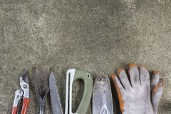 Gardening tools,shovel,gloves,shears,saw on concrete floor. Top view Royalty Free Stock Photo