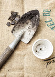Gardening tools soil and pot plant on sack background Stock Photos