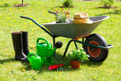 Gardening tools and a straw hat. On the grass in the garden Royalty Free Stock Images