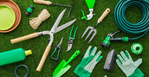 Gardening tools. And utensils on a lush green meadow, top view, garden manteinance, landscaping and hobby concept Royalty Free Stock Photo