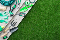 Gardening tools. And utensils on a wooden table and lush meadow, hobby and garden manteinance concept Royalty Free Stock Photography