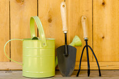 Gardening Tools. With watering can, trowel, and hand cultivator on wood background Stock Photography