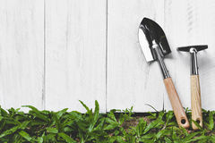 Gardening tools and wooden plank on grass Royalty Free Stock Photos