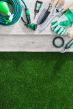 Gardening tools. On a wooden table and lush grass, hobby and garden manteinance concept Royalty Free Stock Photo