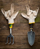 Gardening tools in working gloves on wooden Stock Photo