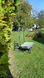 Gardening in France. Wheelbarrow, stepladder and chainsaw against recently cut hedge in French garden in sunshine with flowers and trees in background Stock Image