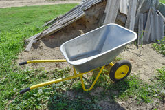 Gardening wheelbarrow for transportation of sand and earth. Two-wheel yellow car.  Stock Image