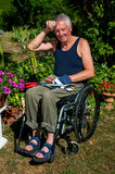 Gardening in Wheelchair. Retired person in a wheelchair starts to sweat during gardening Royalty Free Stock Images