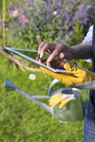 Gardening woman senior using a digital tablet computer in her ga Stock Images