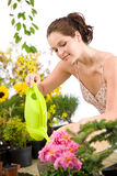Gardening - woman with watering can and flowers Royalty Free Stock Photos