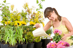 Gardening - woman with watering can pouring water Stock Image