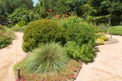 Gardens can soothe the soul. A large flower bed that divides a gravel walkway Stock Images