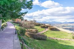 The gardens of Lorca Castle. In southern Spain, showing walkways that cris-cross the lawn, with a wall on the far-side and the view down below royalty free stock photography