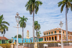 The gardens in Plaza Mayor -main square in Trinidad. Trinidad, Cuba -March 8, 2016: Beautiful architecture of Palacio Brunet in Trinidad and the bell tower of Royalty Free Stock Image