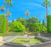 Gardens of Royal Alcazar in Seville and Grotto Gallery  Galeria. Seville, Spain - June 09, 2017 : View of big and beautiful garden - Gardens of Royal Alcazar in Royalty Free Stock Photo