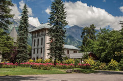 Gardens in Saint-Gervais-Les-Bains with alpine mountains landscape. And building in the background, French Alps, blue sky and clouds royalty free stock images