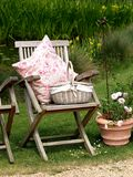 Gardenscene. Pillow and basket on a teak chair Royalty Free Stock Photos