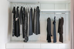 Garderob med raden av den svarta klänningen som hänger på laghängare Royaltyfri Bild