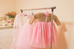 Garderobe für ein kleines Mädchen, Kleider hängen an einem Aufhänger lizenzfreie stockfotos