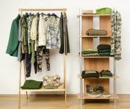 Garderobe met de kleren, de schoenen en de toebehoren van het camopatroon. stock afbeelding