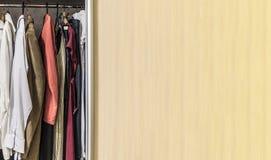 Garderobe met kleren die hangen stock afbeeldingen