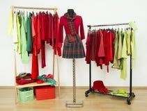 Garderobe mit den ergänzenden roten Farben und grüner Kleidung vereinbarte auf Aufhängern Stockbild