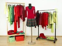 Garderobe mit den ergänzenden roten Farben und grüner Kleidung vereinbarte auf Aufhängern Stockbilder
