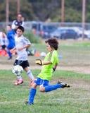 Gardien de but du football du football de la jeunesse donnant un coup de pied la boule Photos stock