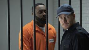 Gardien de prison donnant la dose masculine emprisonnée par Afro-américain d'activité illégale de drogues banque de vidéos