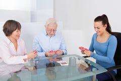 Gardien jouant des cartes avec les couples supérieurs Photo libre de droits