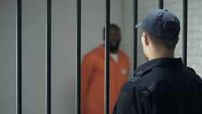 Gardien regardant le criminel dangereux marchant en cellule, condamnation à perpétuité, prison clips vidéos
