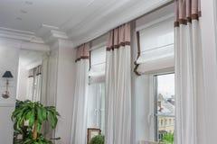 Gardiner i inre, hänger upp gardiner inregarnering i vardagsrum arkivfoto