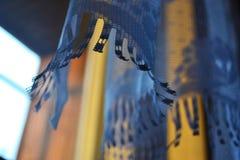 Gardinerna i ljuset av inställningssolen, fokus på kanten av gardinerna, färger är blåa och gula arkivbilder