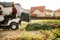 Gardner che per mezzo del trattore del prato inglese e tagliando erba nel giardino durante il tempo di fine settimana Fotografie Stock