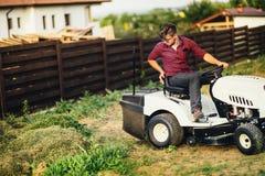 Gardner com cortador de grama, corte profissional do trabalhador e grama do descarregamento Fotos de Stock