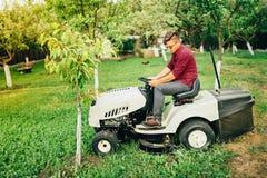 Gardner gebruikend grasmaaimachine voor het schoonmaken en modellerend de werken stock afbeelding