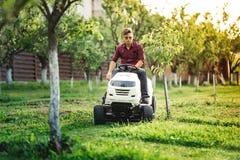 Gardner klippgräs och genom att använda den yrkesmässiga rideongräsklipparen och göra landskap arbeten Royaltyfri Bild