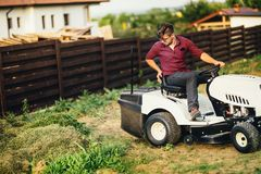 Gardner with lawn mower, professional worker cutting and unloading grass. Man with lawn mower, professional worker cutting and unloading grass Stock Photos