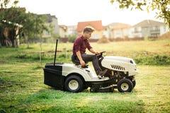 Gardner maaiend gazon met rit-op tractor stock fotografie