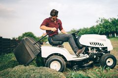 Gardner que faz ajardinando trabalhos e cortando a grama, descarregando a grama Fotos de Stock Royalty Free