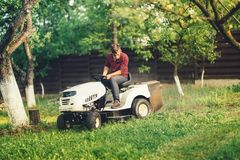 Gardner using lawn mower and premium tools for grass cutting. Professional gardner using lawn mower and premium tools for grass cutting Royalty Free Stock Photos