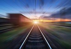 Gare ferroviaire avec des chariots de cargaison dans l'effet de tache floue de mouvement au coucher du soleil Photos libres de droits