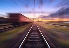 Gare ferroviaire avec des chariots de cargaison dans l'effet de tache floue de mouvement au sunse Photos stock