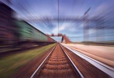 Gare ferroviaire avec des chariots de cargaison dans l'effet de tache floue de mouvement au sunse Image stock